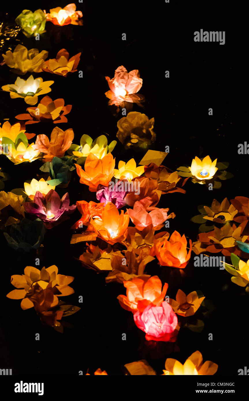 Paper Lotus Flowers With Candles Float On A River At Night To Mark