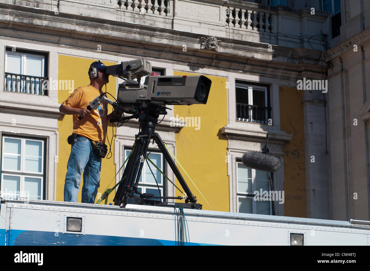 Cameraman on top of building covering the peaceful protest organised by the CGTP union gathers activists in Lisbon - Stock Image