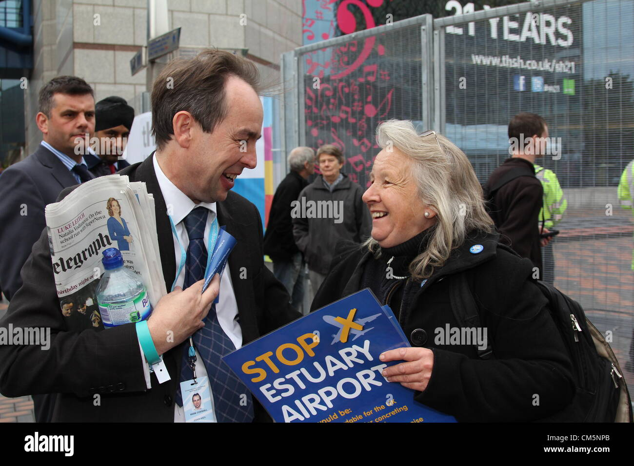 "A Conservative member shares a joke with a ""Stop Estuary Airport"" campaigner outside the Conservative Party Conference Stock Photo"