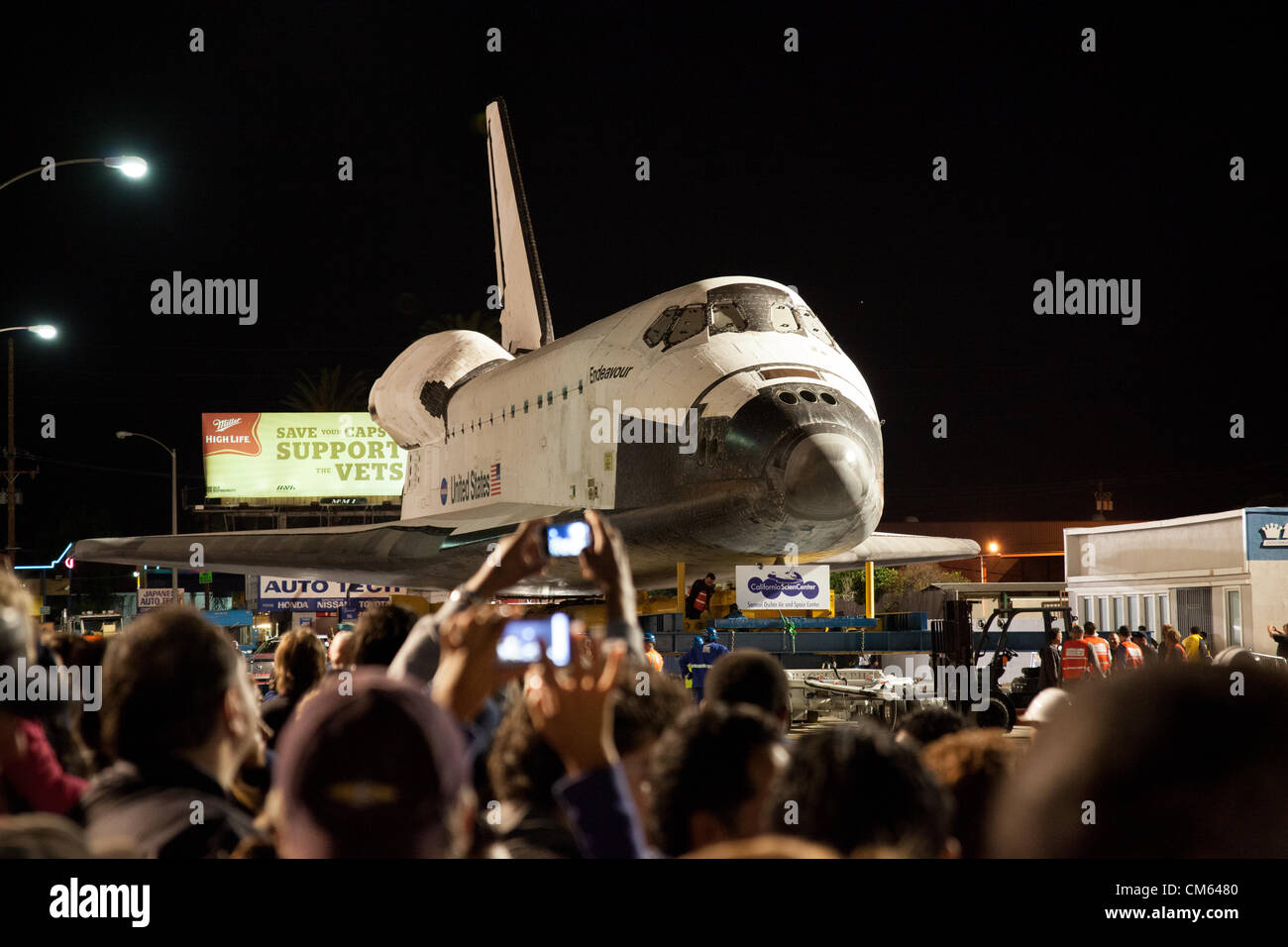 Inglewood, Los Angeles, CA, USA- 12 October, 2012 - The Space Shuttle Endeavour is towed through the streets of Los Angeles on its way to its permanent home at the California Science Center, making a nighttime stop at La Cienega and Manchester Blvd where a Toyota Tundra truck will replace the heavier transport to tow it across the bridge over the 405 Freeway. The Shuttle was decommissioned in 2011 when the NASA space program was discontinued. Stock Photo