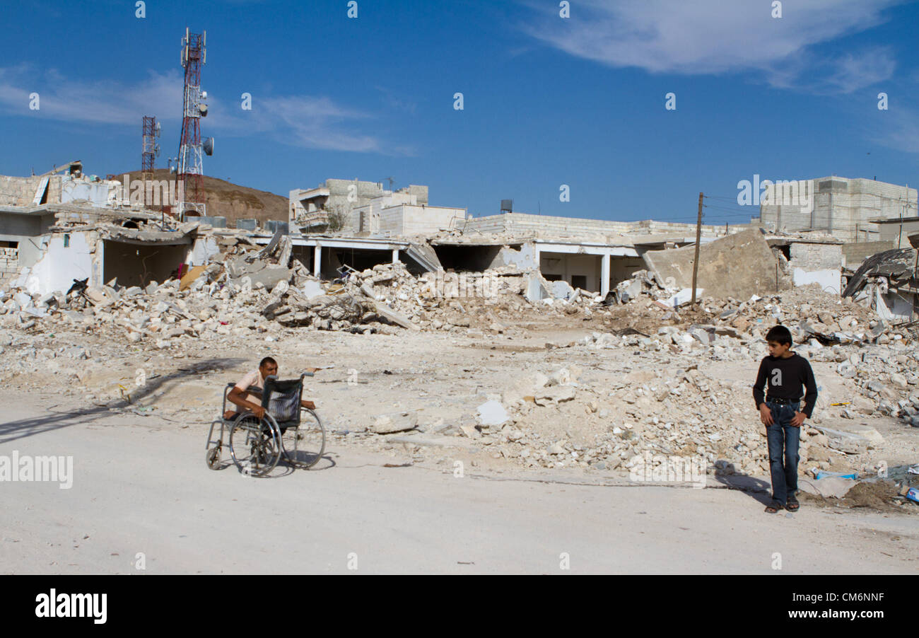 Azaz, Syria. 17th October 2012. A man rolls his wheel chair by buildings destroyed by MIG fighter jets.  Many people - Stock Image