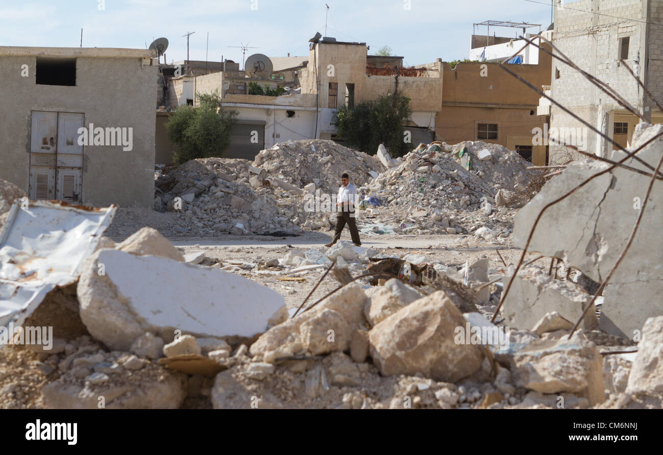 Azaz, Syria. 17th October 2012. A man walks by buildings destroyed by MIG fighter jets.  Many people died in these - Stock Image