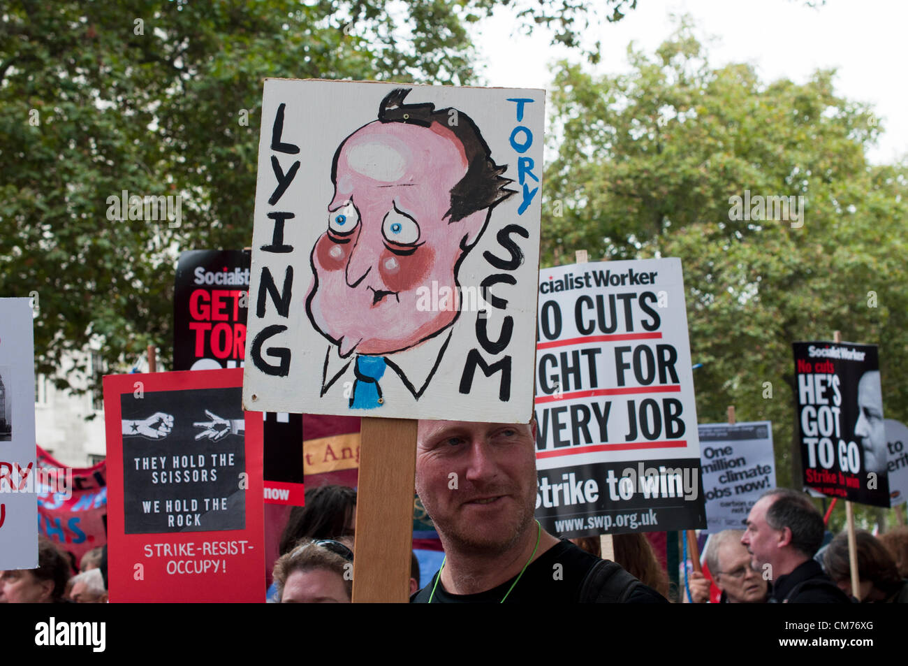 20/10/2012, London UK. A man brandishes a placard with an unflattering hand painted portrait of David Cameron as - Stock Image