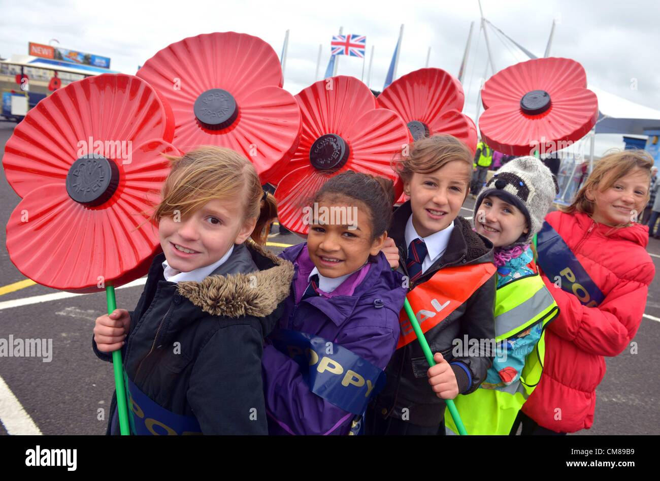 School children holding giant poppies as part of Remembrance Royal British Legion appeal - Stock Image