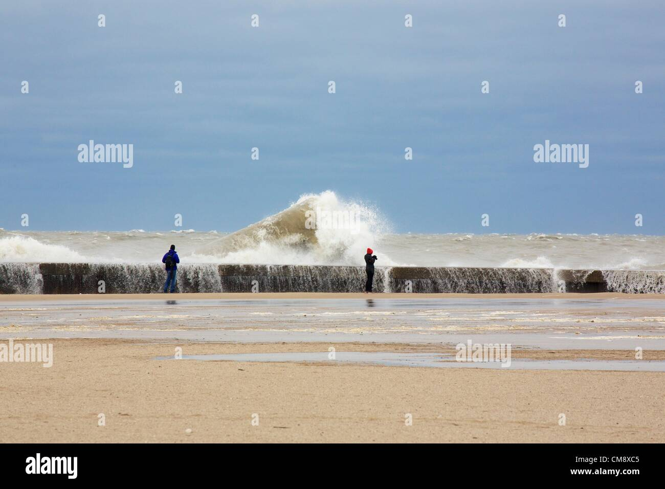 Chicago, Illinois. 30th October, 2012.  Large waves crash into the seawall at North Avenue Beach as photographers - Stock Image