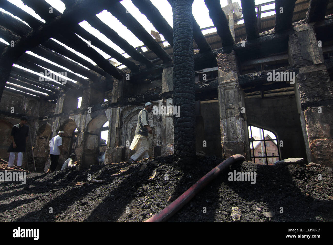 Kashmiri Muslim volunteers helps clear debris inside the charred remains of the 200-year old shrine of Sheikh Abdul - Stock Image