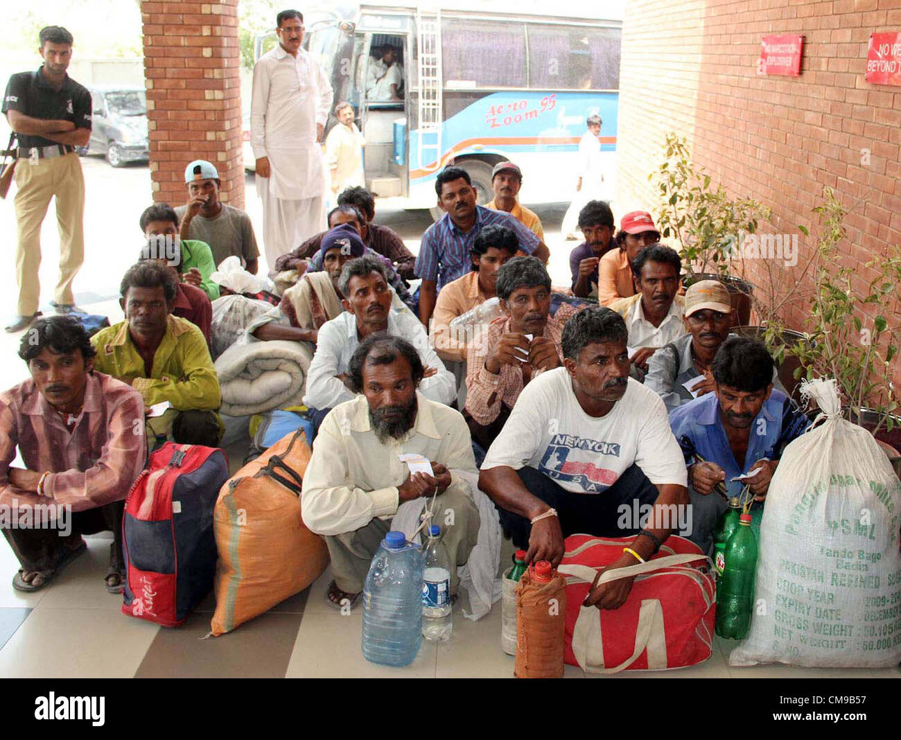 Freed Indian fishermen, who were imprisoned for violating  territorial waters, sit at Wagah border in Lahore on - Stock Image