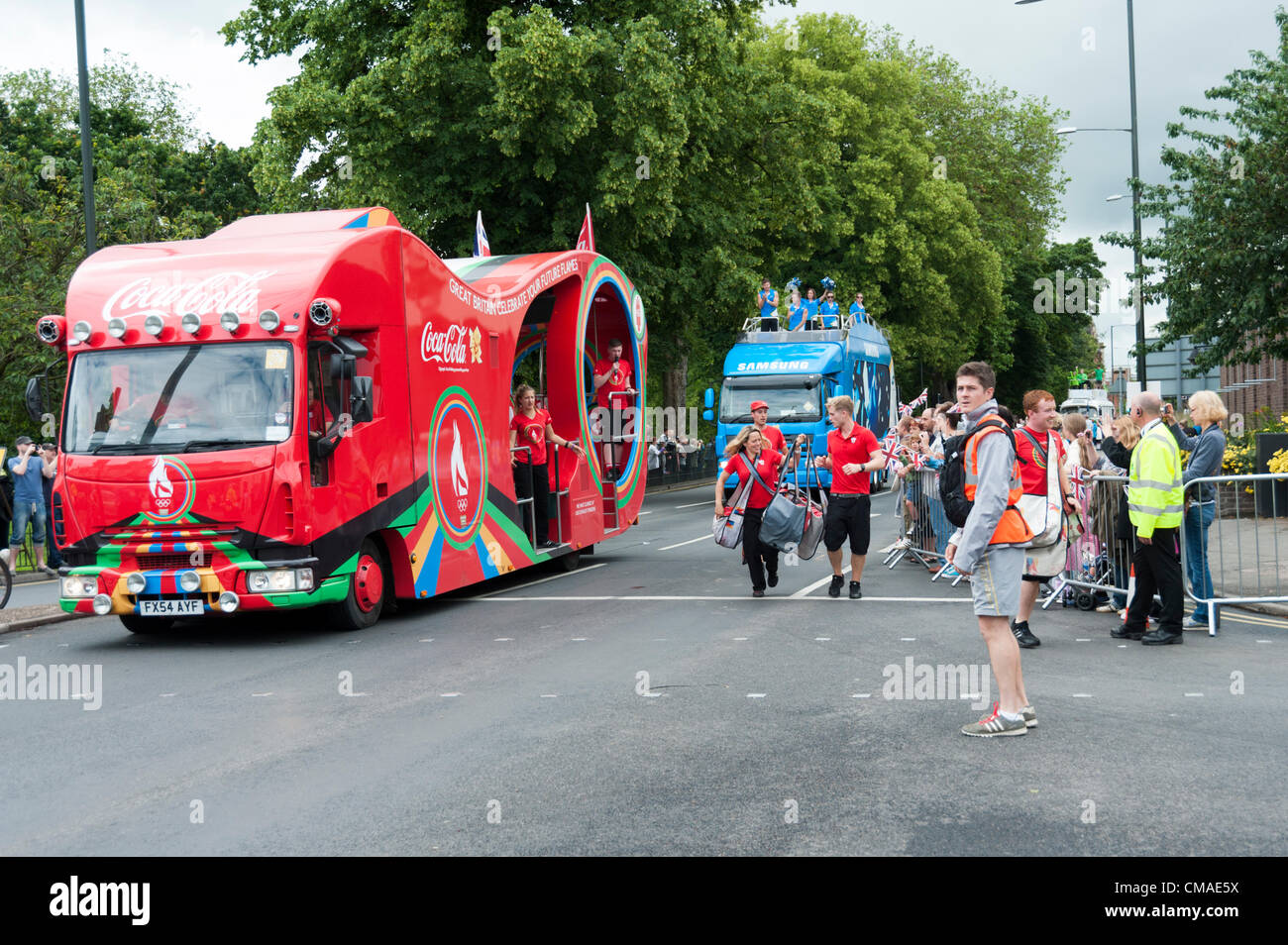 The Olympic Torch comes to Kings Lynn Norfolk July 4th 2012. The Coca Cola and Samsung sponsor vehicles drive along - Stock Image