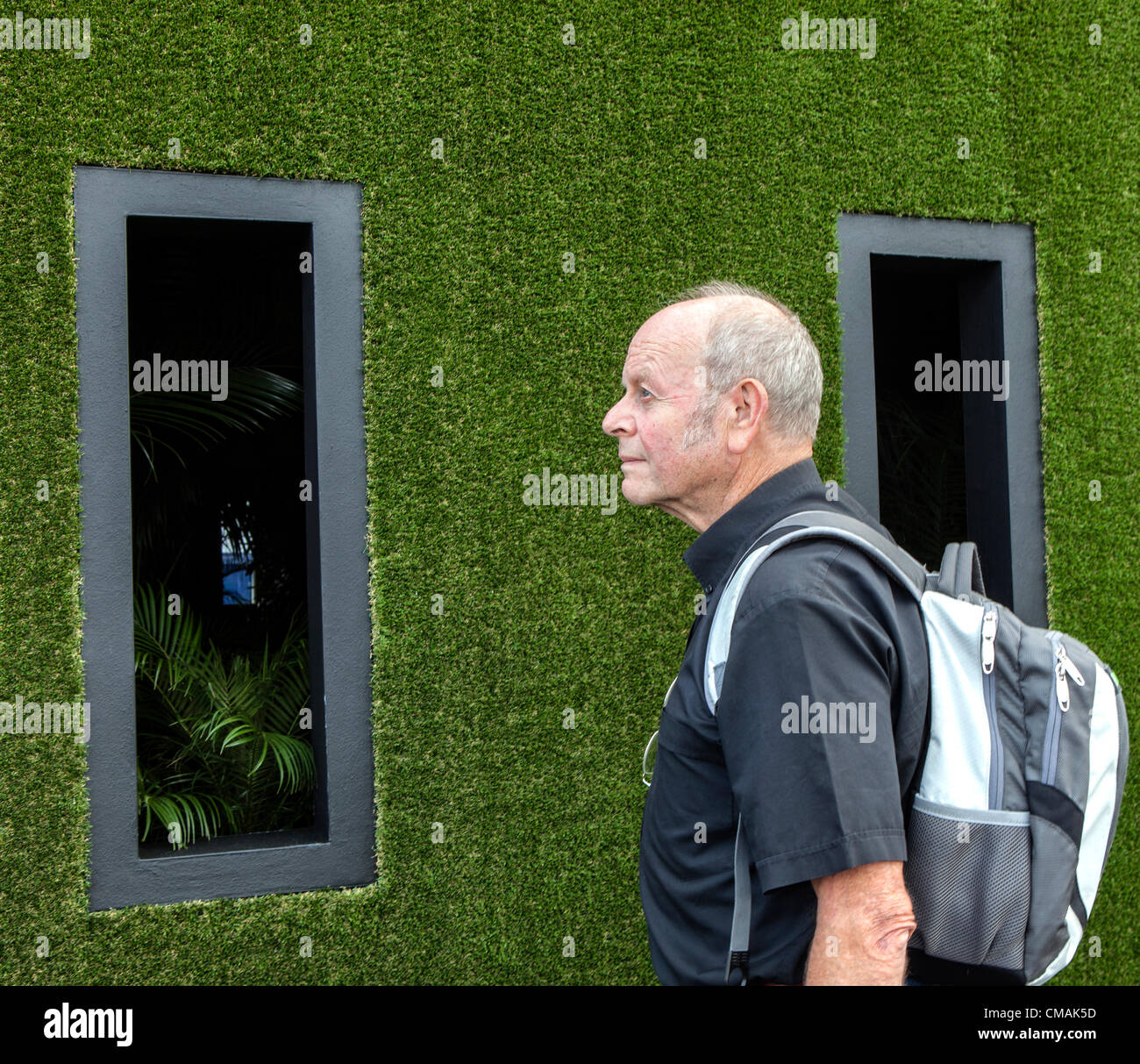 Hampton Court, UK. Wednesday 4th July 2012.  Show visitor admires 'Possession' ,a grass covered exhibit - Stock Image