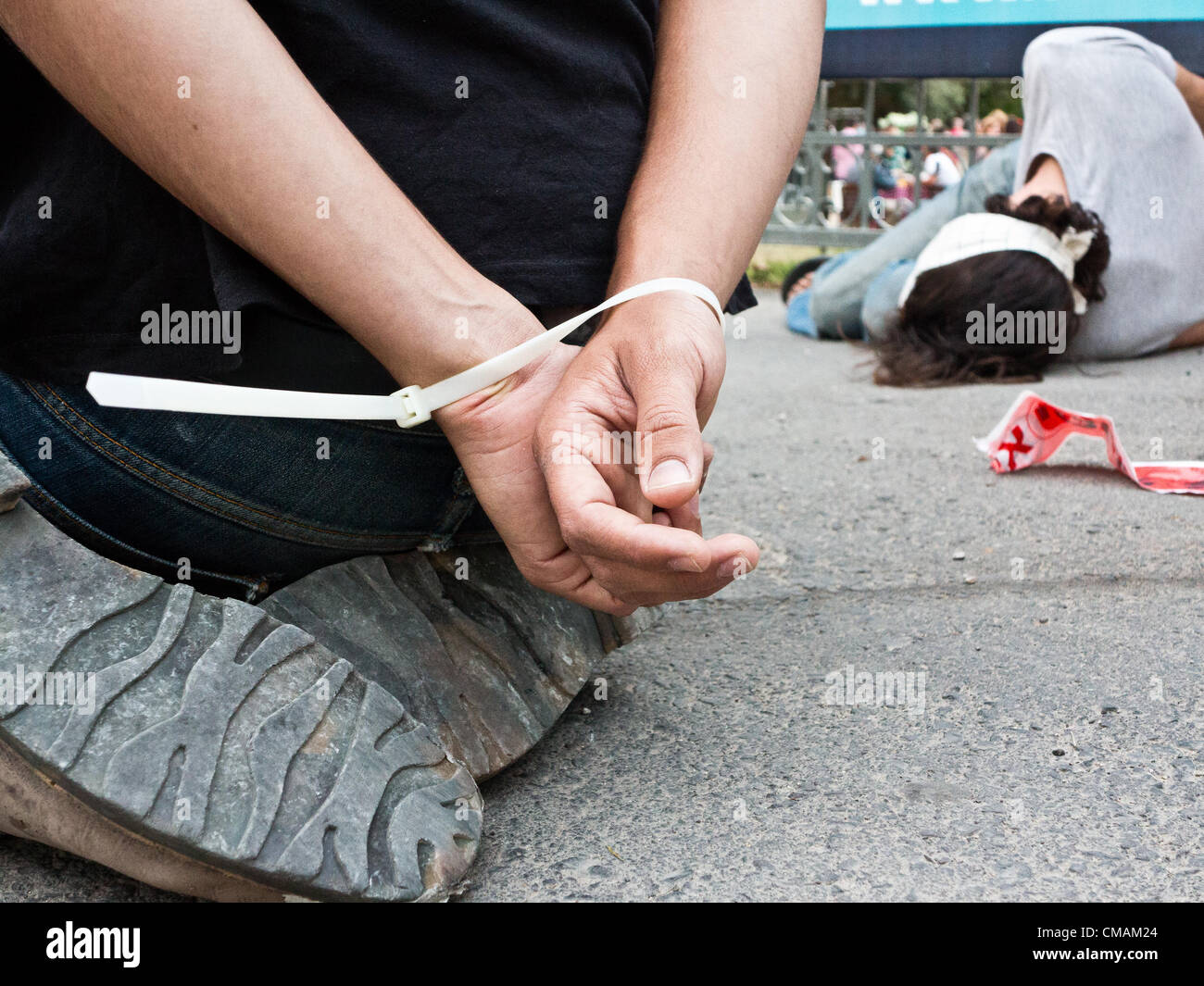 Jerusalem, Israel. 5-July-2012. The hands of a human rights activist-actor are tied behind his back protesting alleged - Stock Image