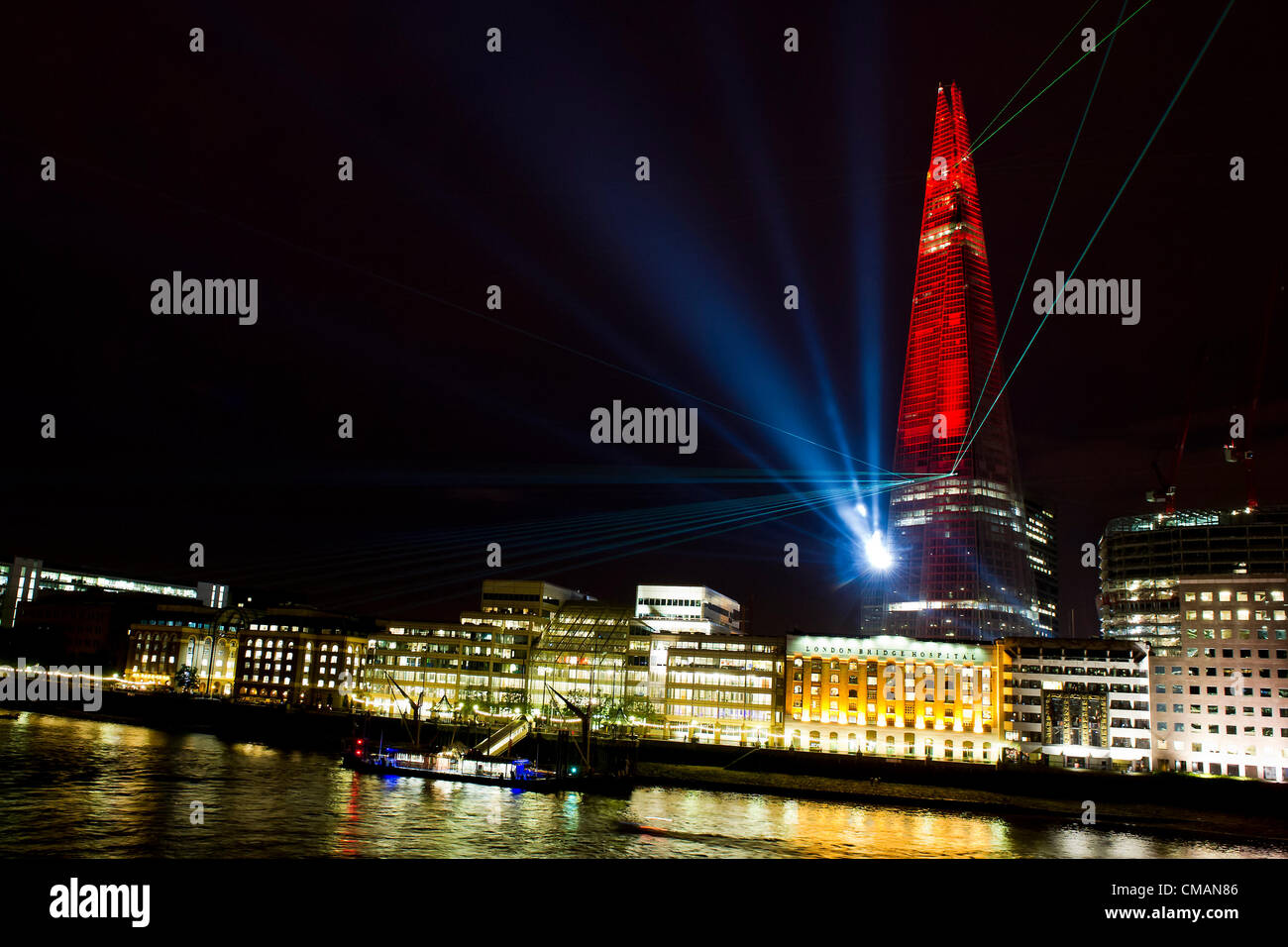 The Shard is illuminated with lasers and lights to mark its completion.  The crowd on the north bank of the River - Stock Image