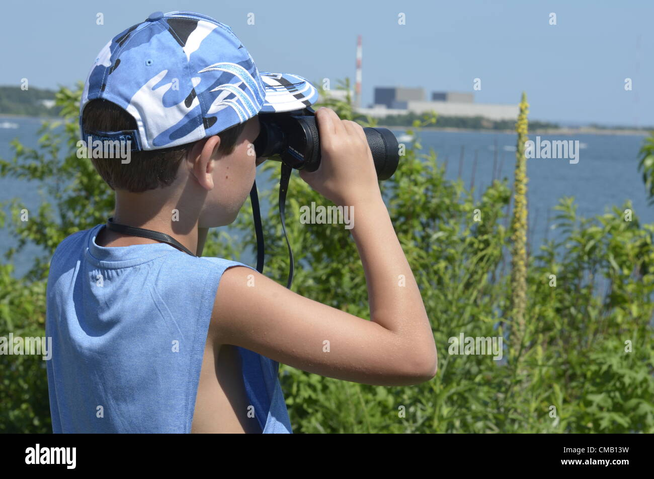 Young explorer. Niantic, Connecticut, USA, July 6, 2012 - From a high vantage point at McCooks Point Park, seven - Stock Image