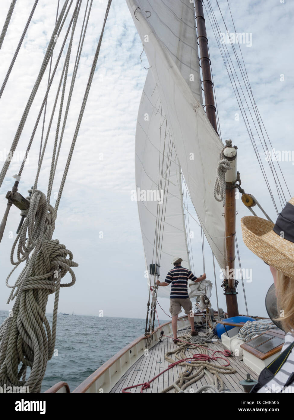 The Honorable Heather Somer, Mayor of Groton, Connecticut looks on as crew member Don Grinberg raises the sails - Stock Image