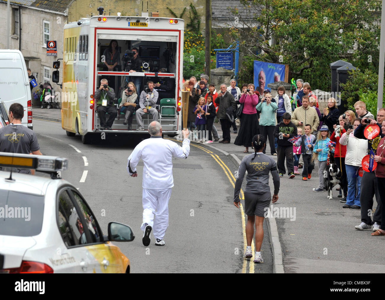Day 56 of the torch relay around the UK…The torch passing through Fortuneswell, Portland in Dorset. Britain. 13/07/2012 - Stock Image