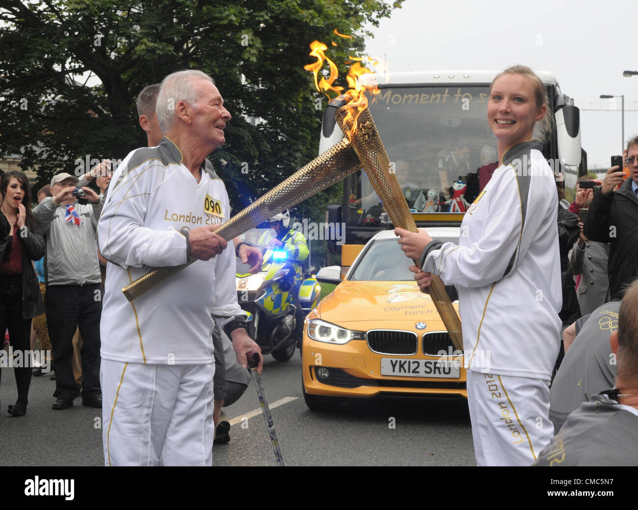 SOUTHAMPTON, ENGLAND - July14: The torch 'kiss' as two runners pass on the flame. Olympic Torch event on - Stock Image