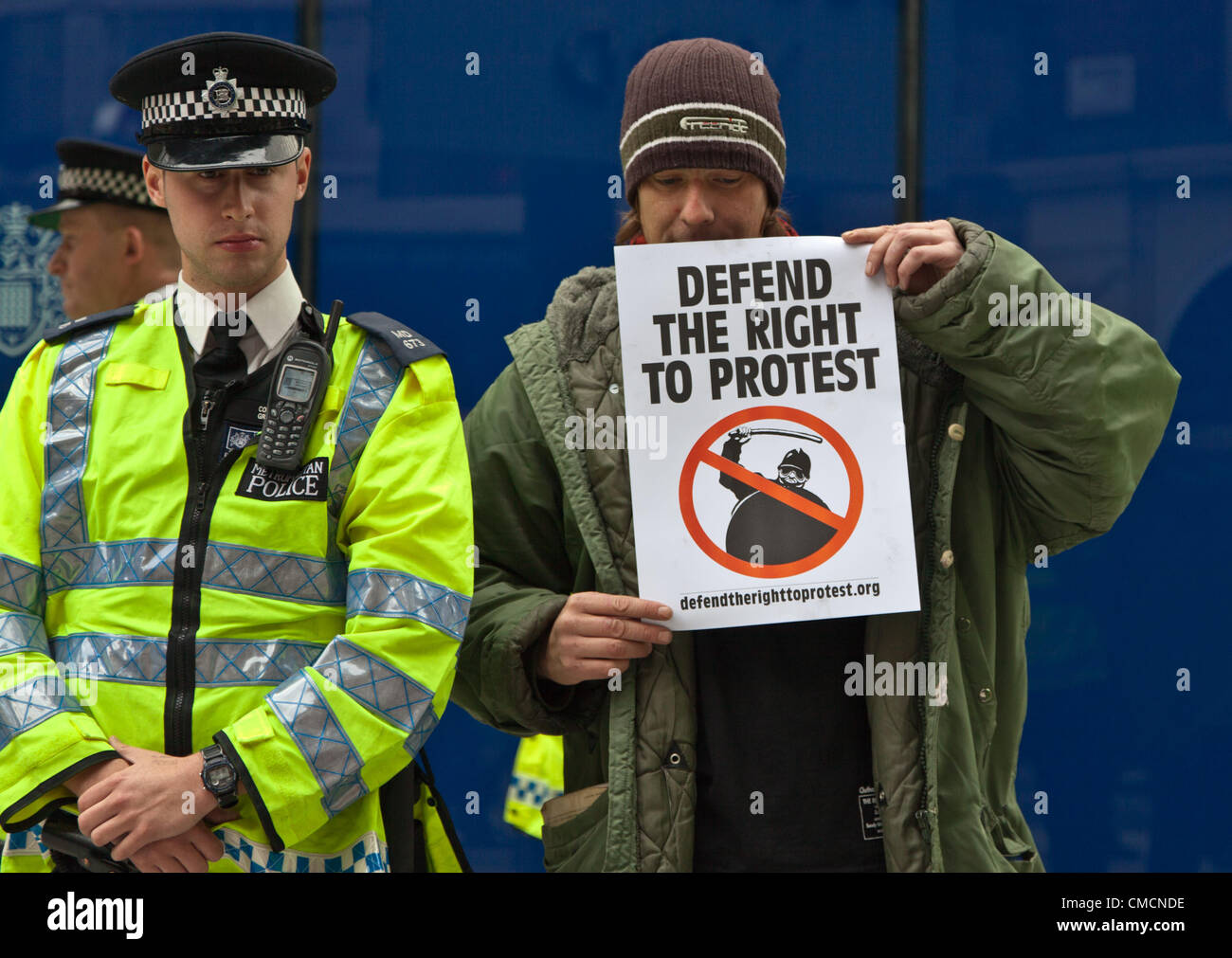 London, UK. 19th July 2012 A protestor hold a sign saying 'Defend the right to protest' next to a police - Stock Image