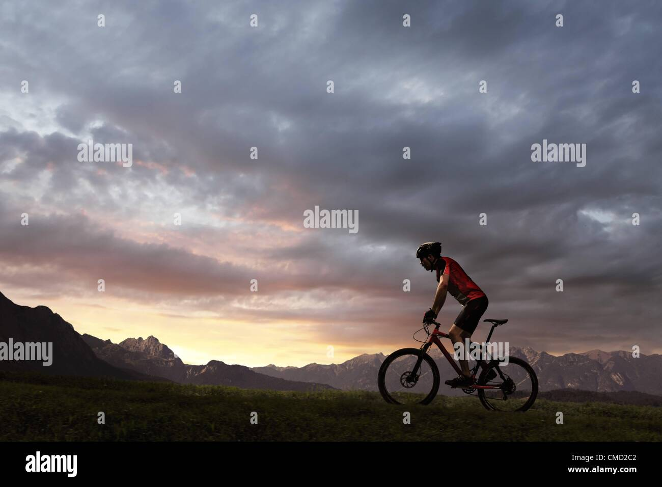 08.11.2011. Germany. Model released picture of a cyclist riding into the setting sun. - Stock Image
