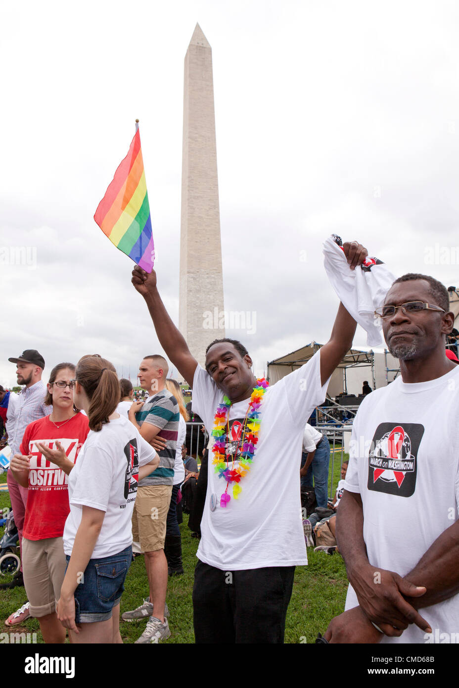 A man waves a rainbow flag in front of the Washington monument in Washington, DC - Sunday, July 22, 2012 Stock Photo