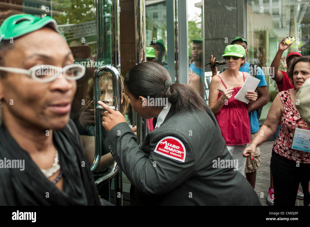 July 24, 2012 - U.S. - A security guard directs a woman in her buidling to another exit as she guards the door at - Stock Image