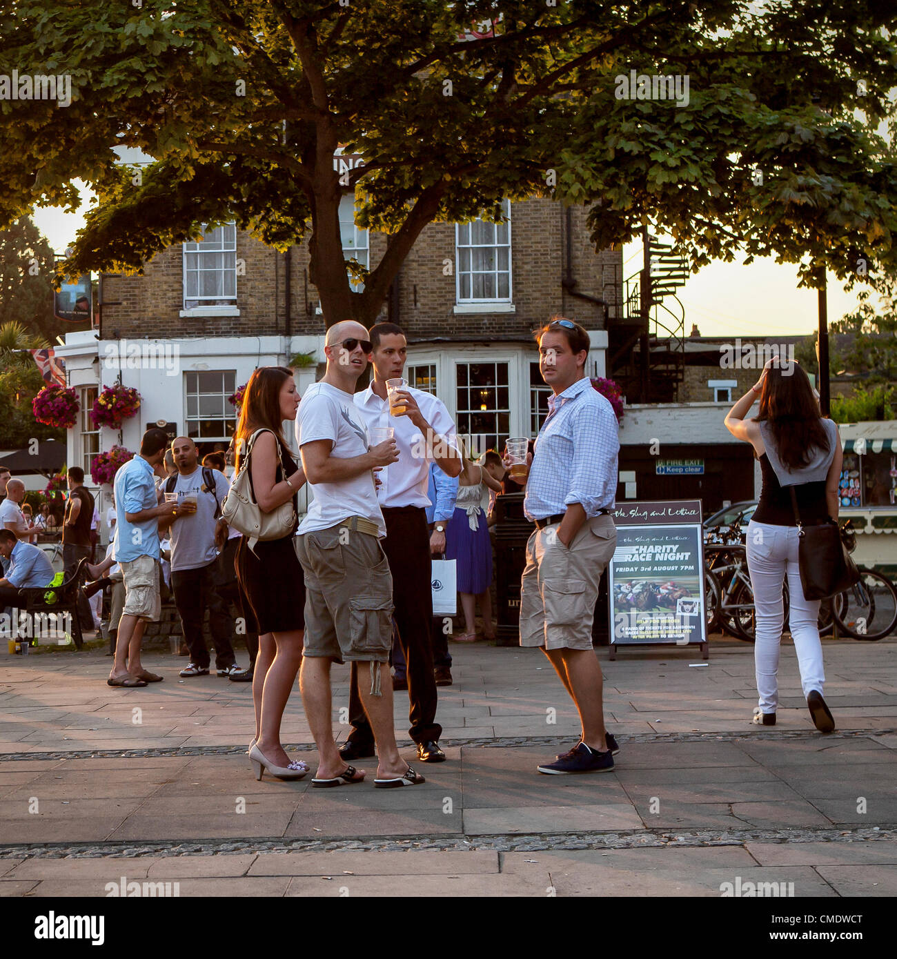 Thames riverside, Richmond Upon Thames, Greater London, UK - 25 July 2012: People left work and hurried down to - Stock Image