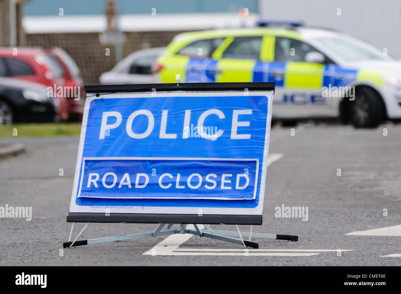 Police road closed sign with police car blocking the road - Stock Image