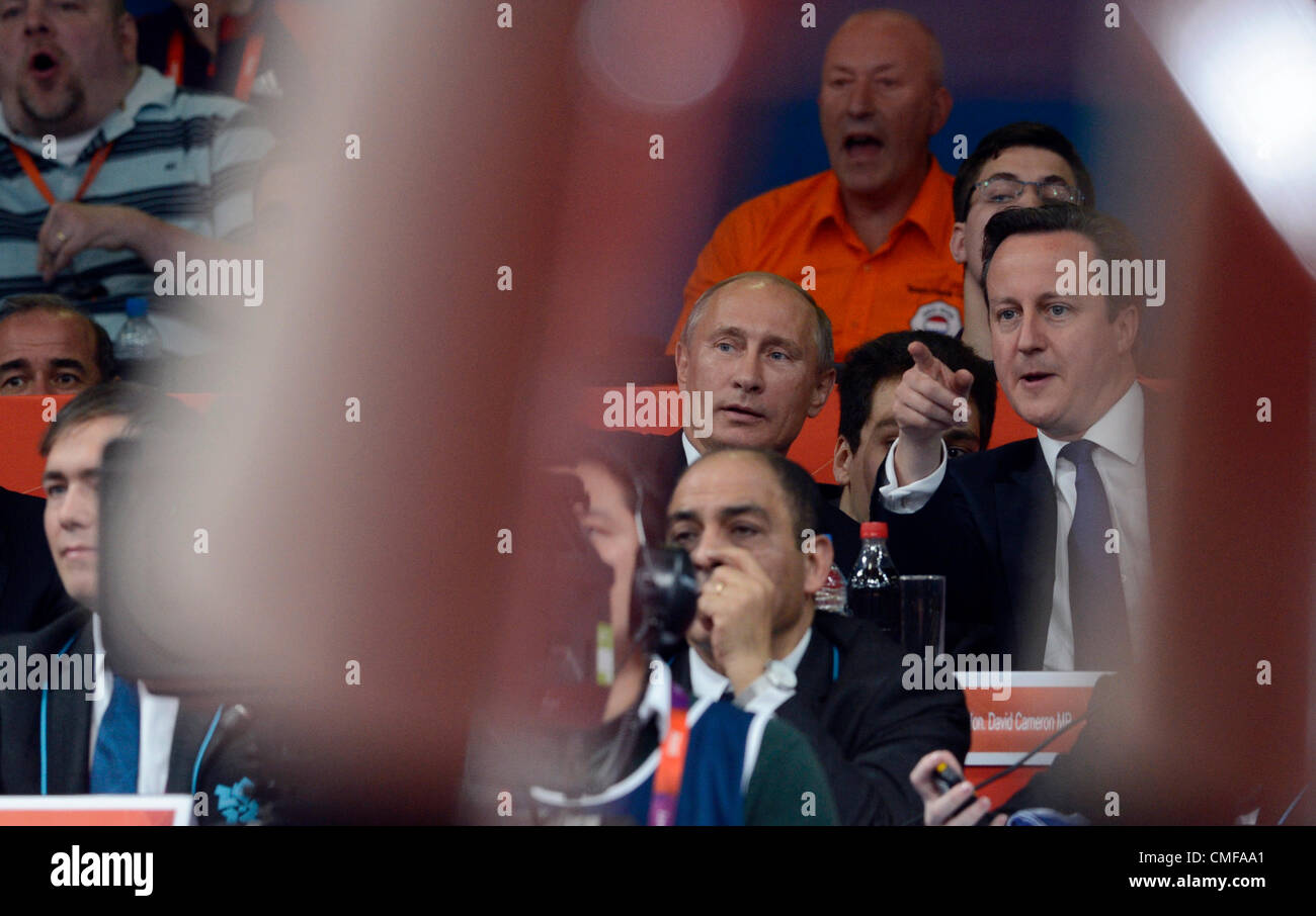 Russian President Vladimir Putin (centre) and British Prime Minister David Cameron watch the men's 100-kg judo competition Stock Photo