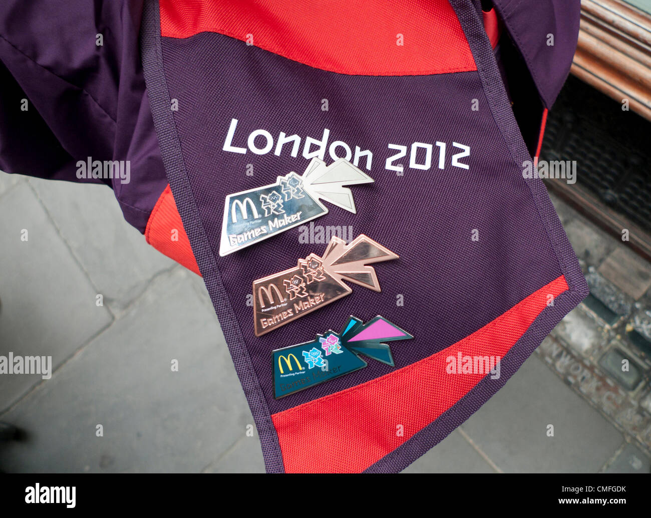 2 Aug 2012- CARDIFF WALES UK- A  2012 London Olympic Games volunteer's purple and red uniform adorned with sponsor - Stock Image