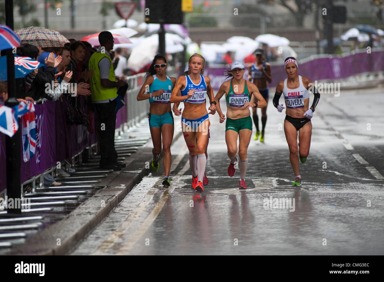 The London Olympic Games 2012 Womens Marathon runners approach the City of London from The Embankment in torrential - Stock Image