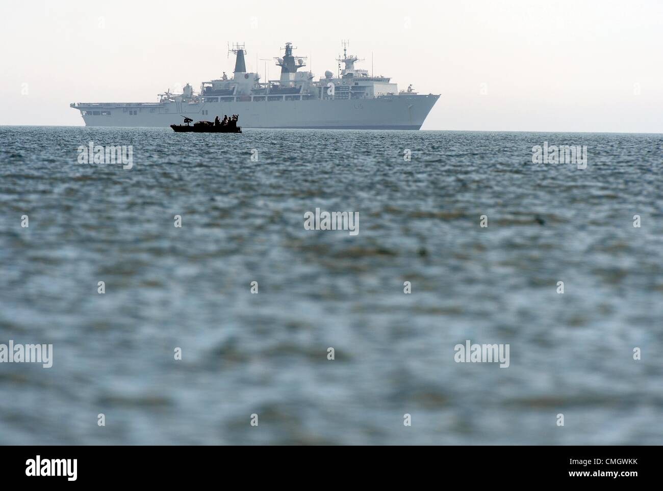 HMS Bulwark and security boat at the 2012 Olympic Games sailing venue - Stock Image