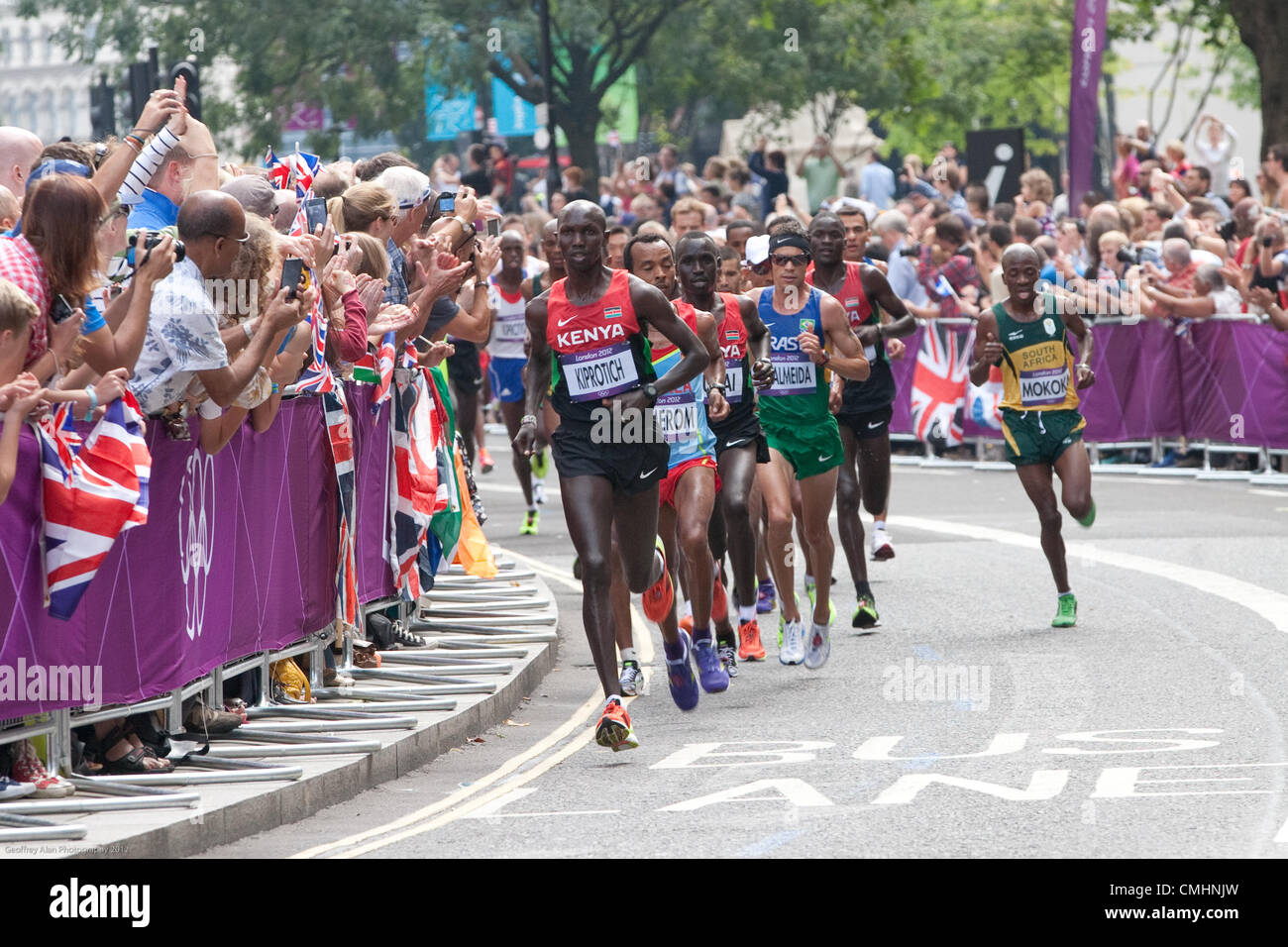 Crowds cheer on as the men's marathon runners pass by St. Pauls Churchyard, City of London at mile 5, 1st lap. Wilson - Stock Image
