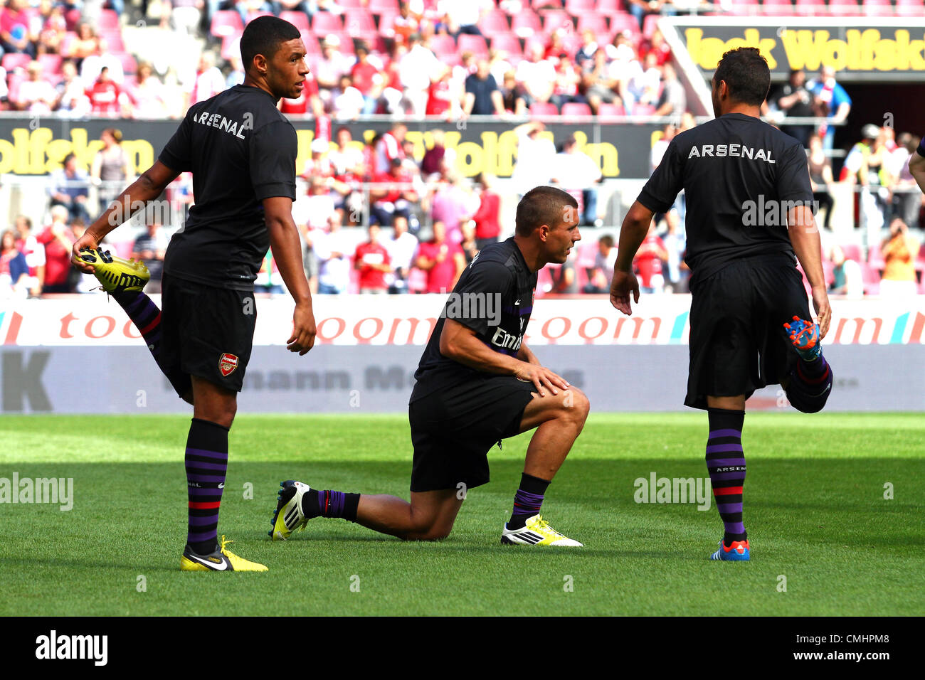 12.08.2012. Cologne, Germany.  Arsenal's Lukas Podolski (C) and his teammates warm up before preseaon friendly - Stock Image