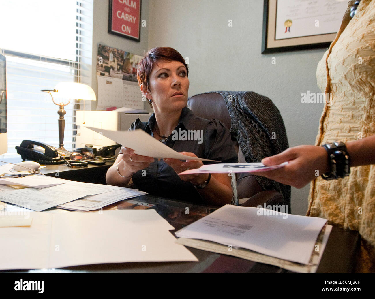 Immigration attorney reviews paperwork regarding Deferred Action for Childhood Arrivals process for client. - Stock Image