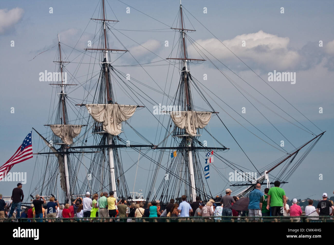 Spectators gather on Castle Island to watch the USS Constitution head out for a commemorative sail in Boston Harbor, - Stock Image