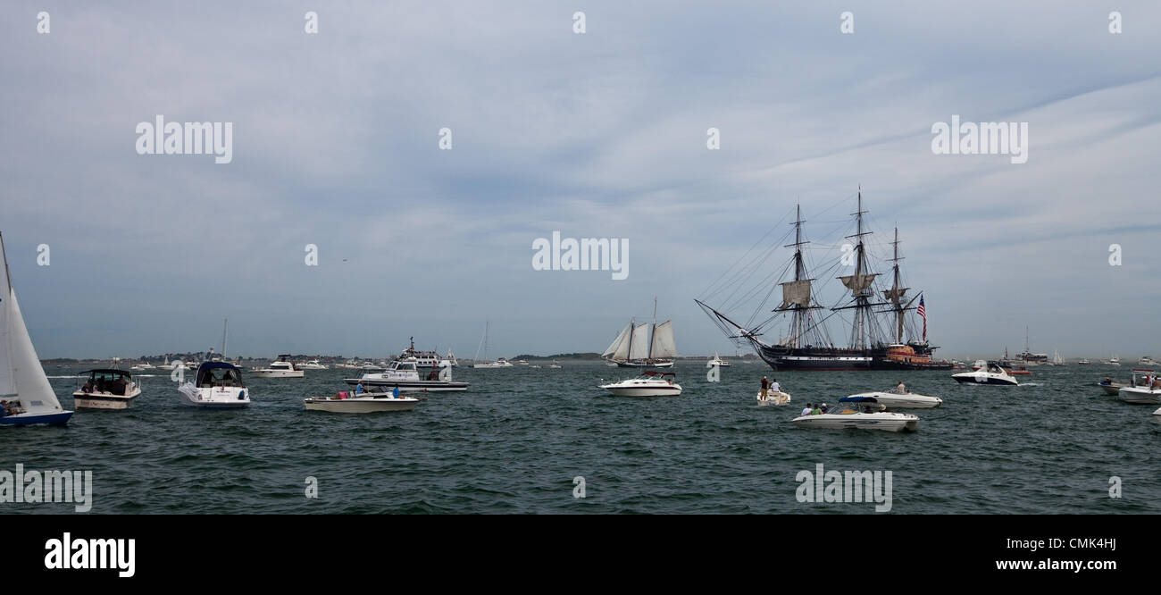Pleasure boats watch the USS Constitution return from a commemorative sail in Boston Harbor, marking the day  she - Stock Image