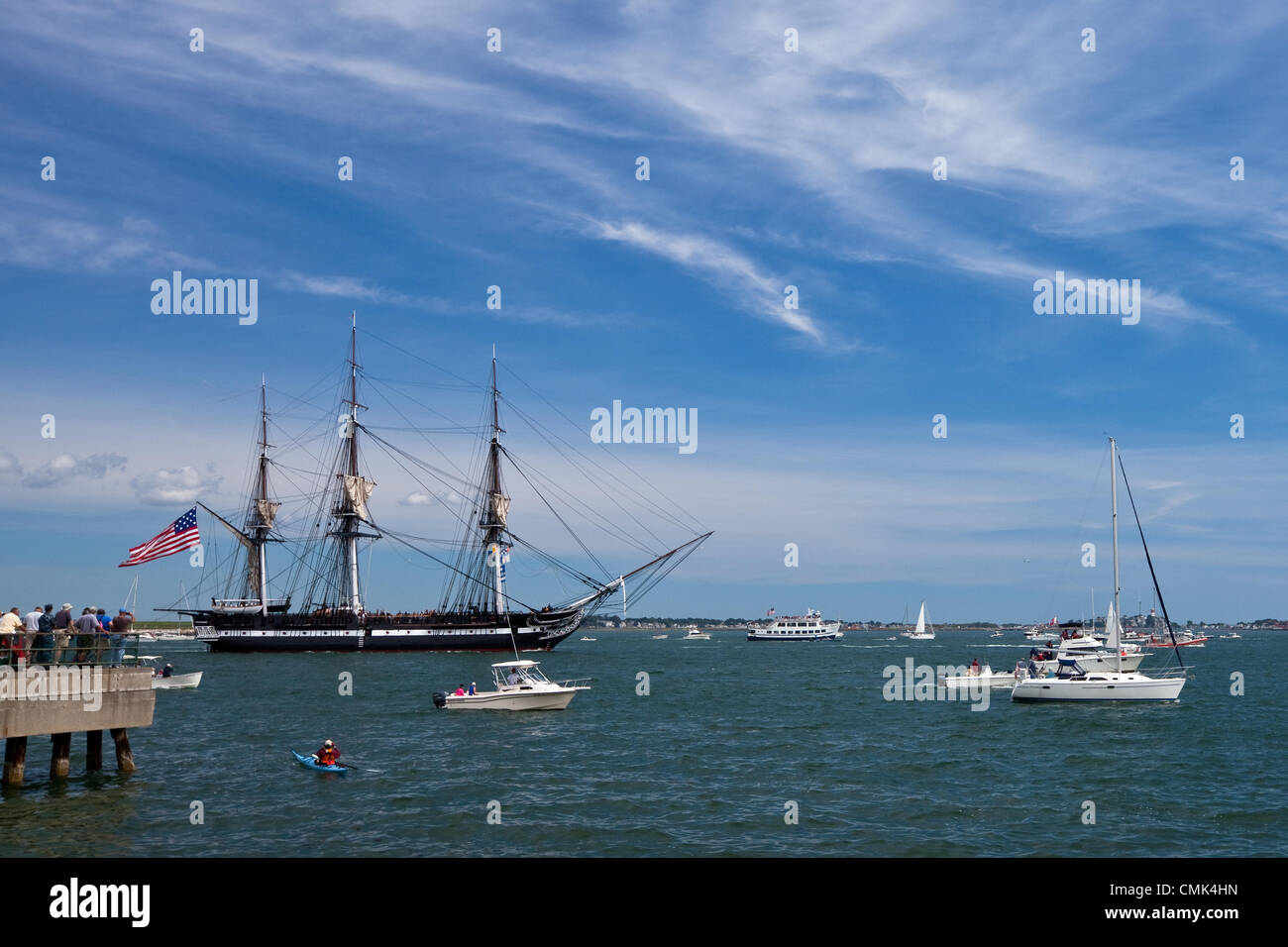 Spectators and pleasure boats gather to watch the USS Constitution head out for a commemorative sail in Boston Harbor, - Stock Image