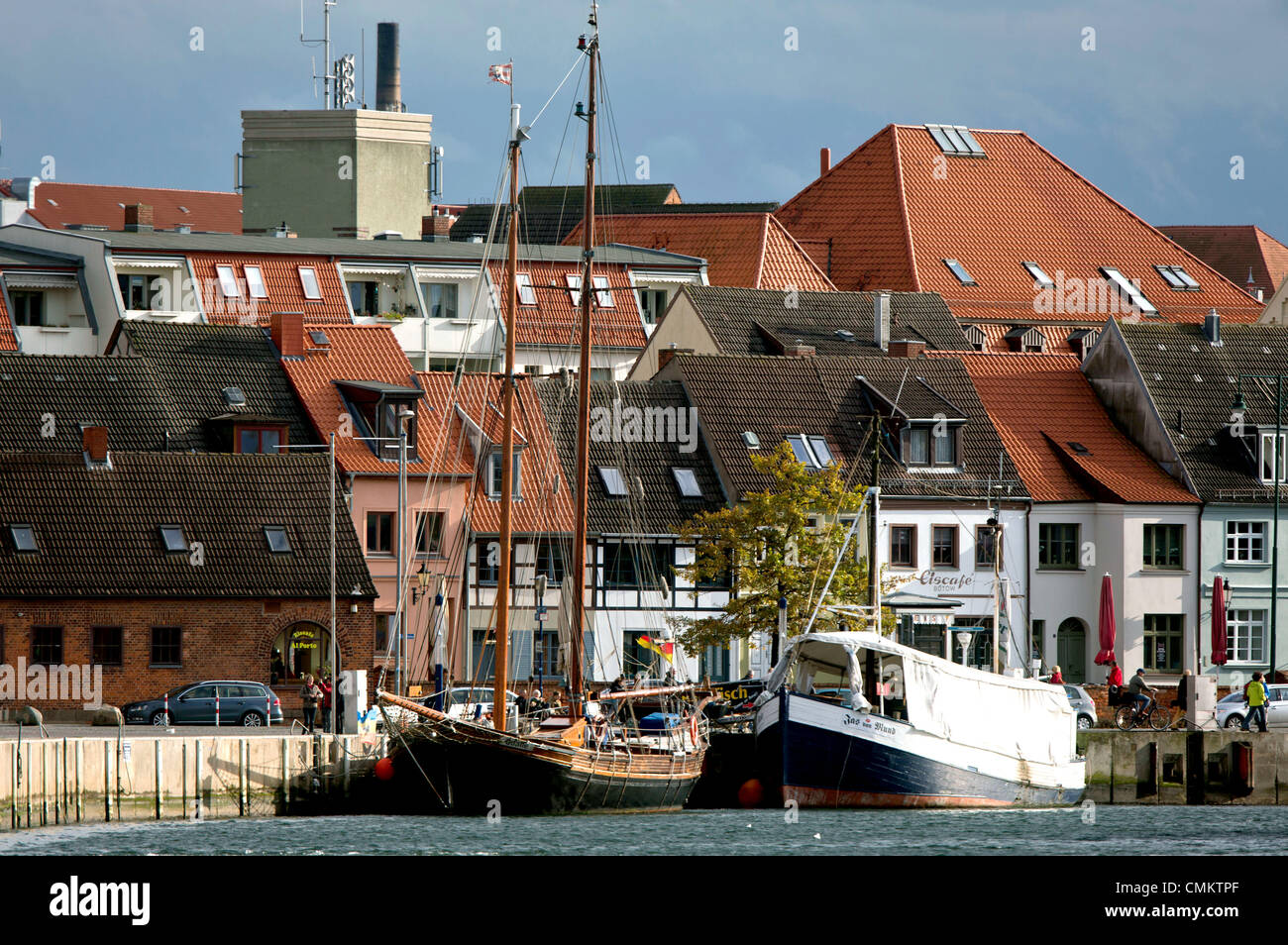 Wismar, Germany. 28th Oct, 2013. A traditional sailing vessel and a fishing boat are moored at the city port of - Stock Image