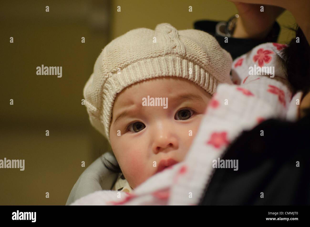 cute mixed asian (korean) caucasian baby girl looks at the