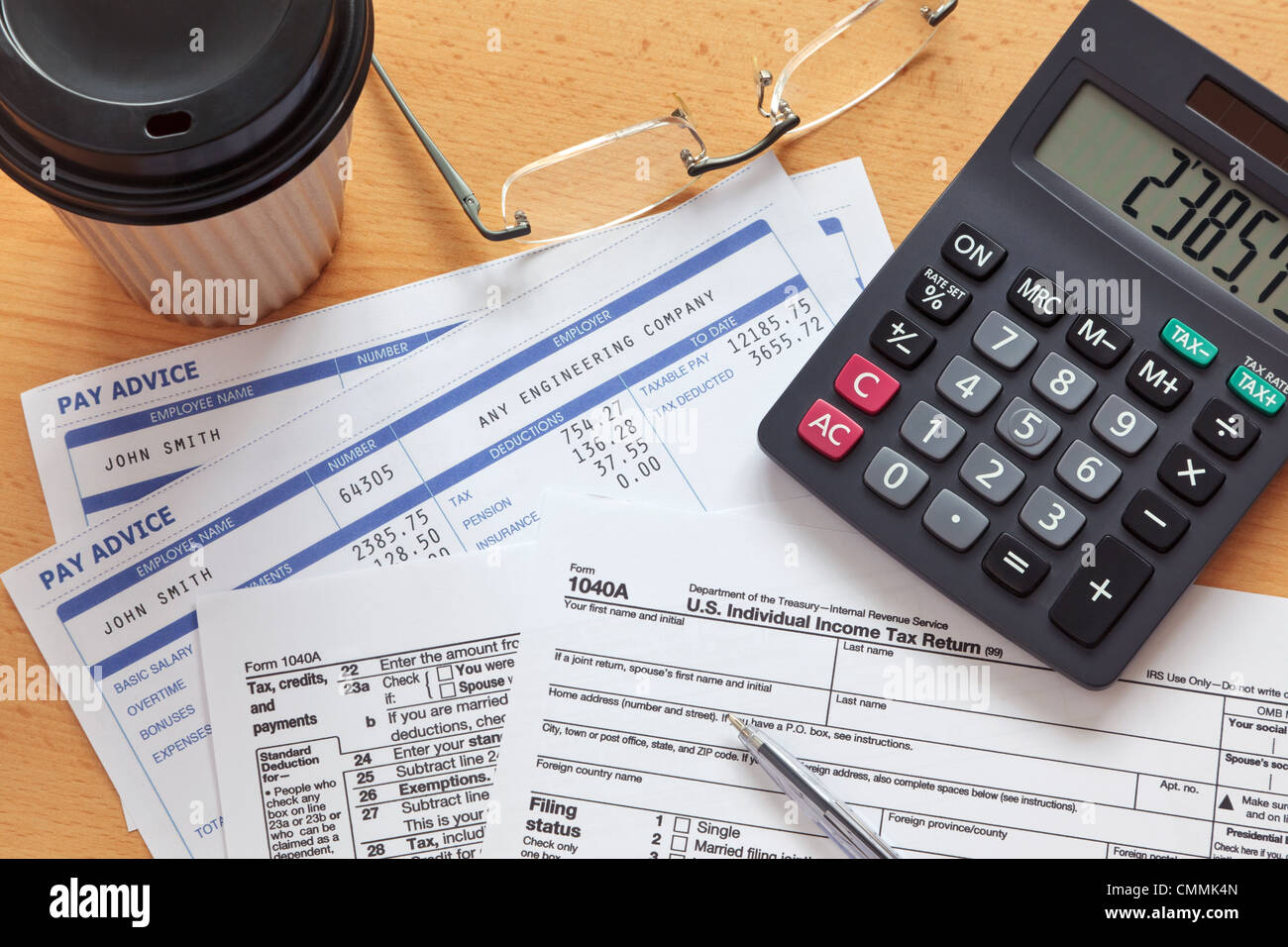Photo of a 1040A tax form with payslips and a calculator. - Stock Image
