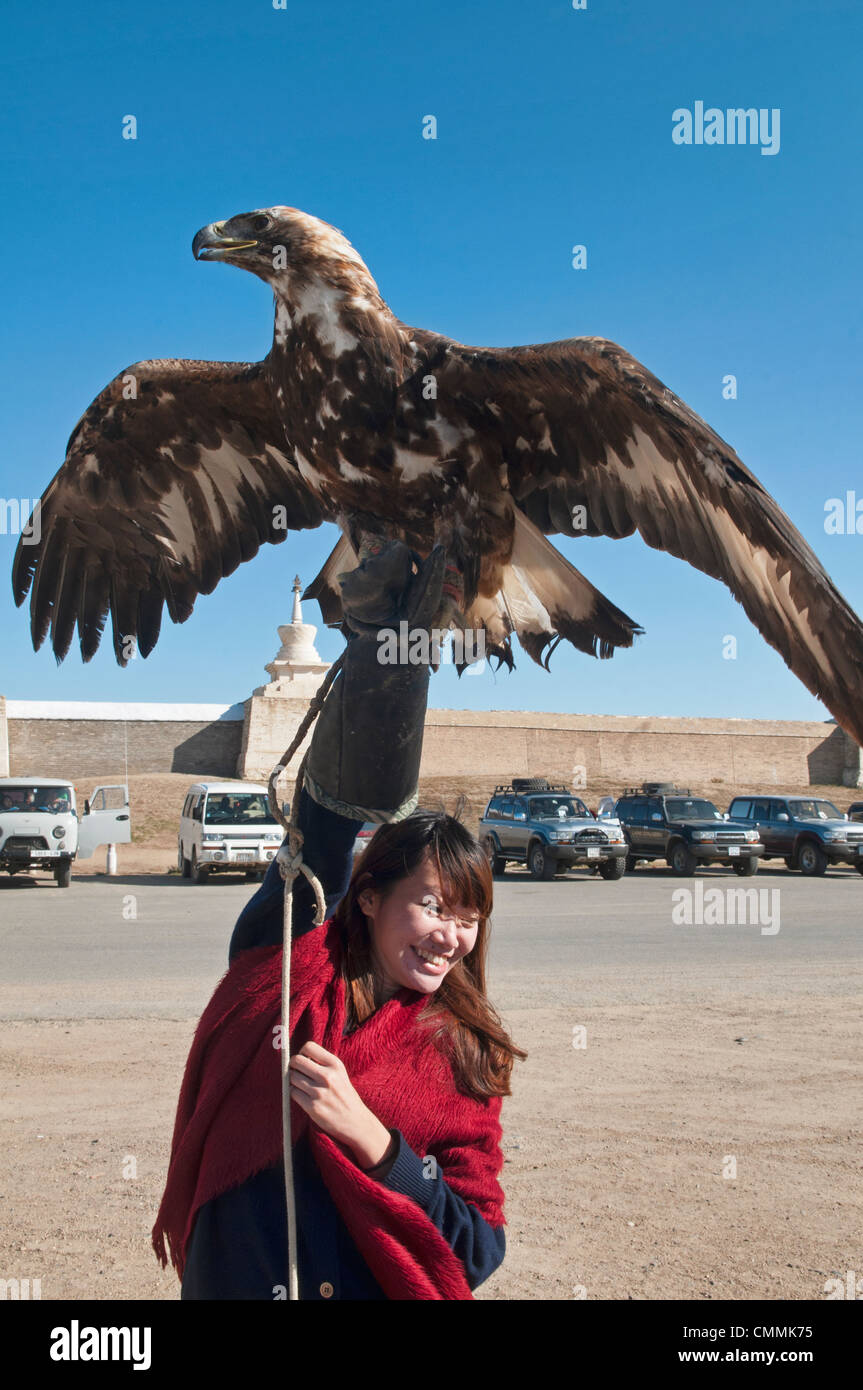 tourist hoisting a golden eagle in the Orkhon Valley of Mongolia - Stock Image