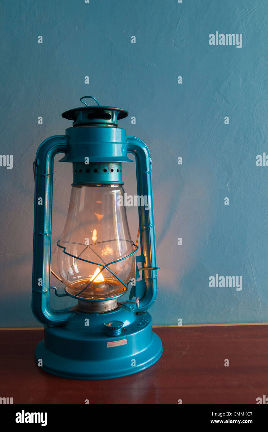 lighted old fashioned kerosene/oil lamp on table with blue background - Stock Image
