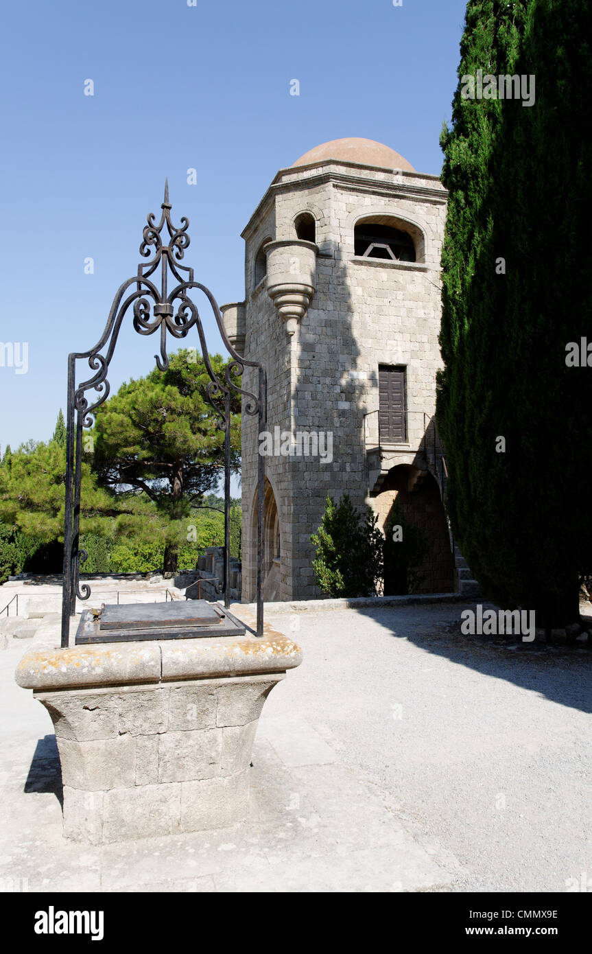 Rhodes. Greece. View of courtyard well and the bell tower of 14th century golden walled Church of our Lady which - Stock Image
