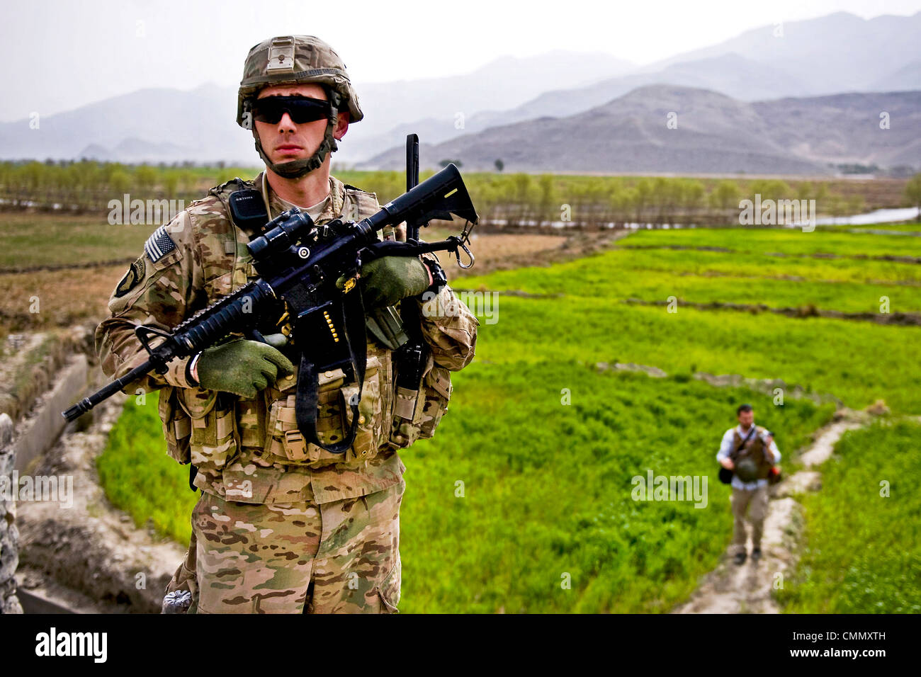 US soldiers provide protection for advisors with the Nagarhar Agribusiness Development Team during a field inspection Stock Photo