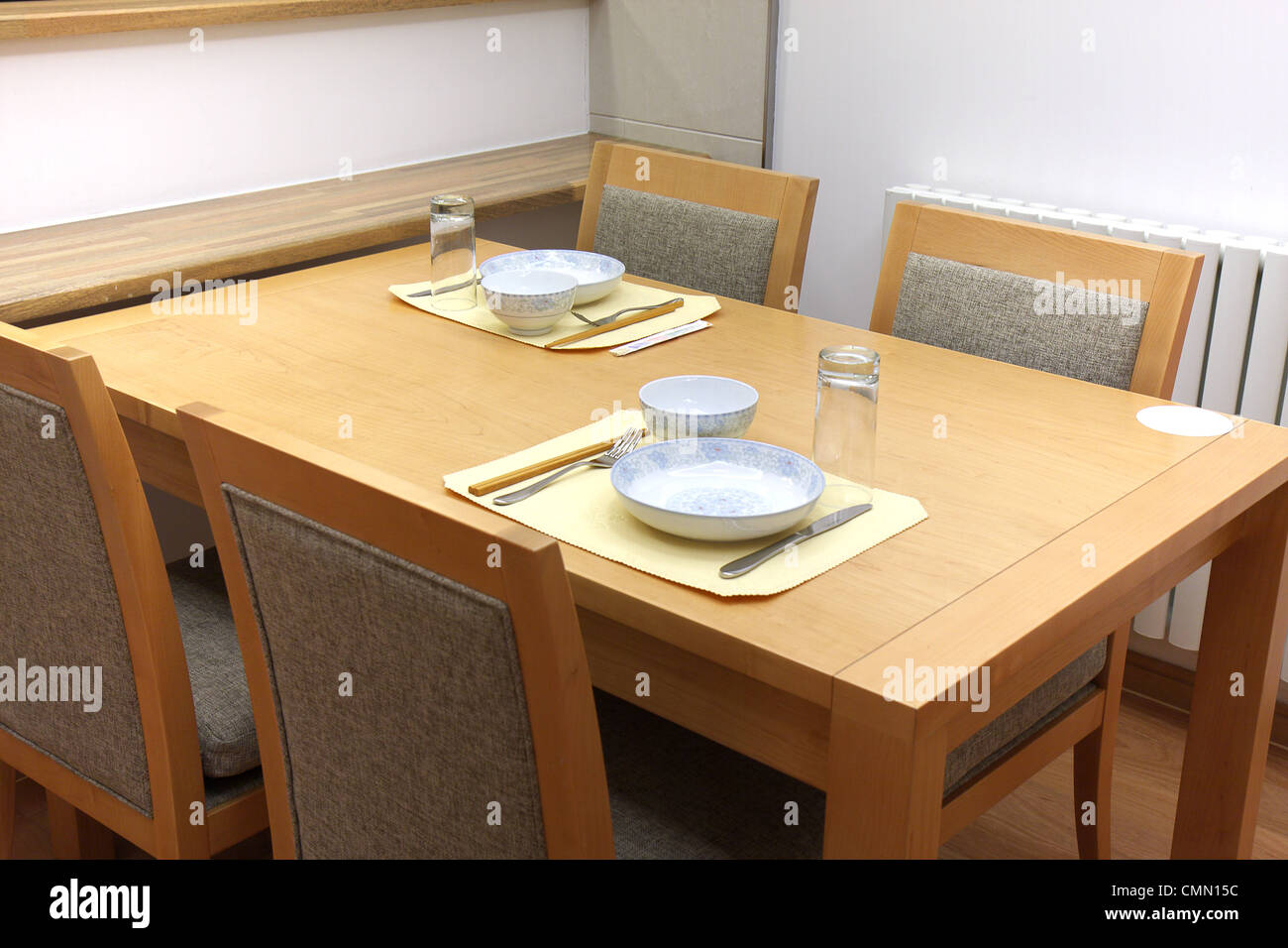 Wooden dining furniture with oriental style utensils. - Stock Image