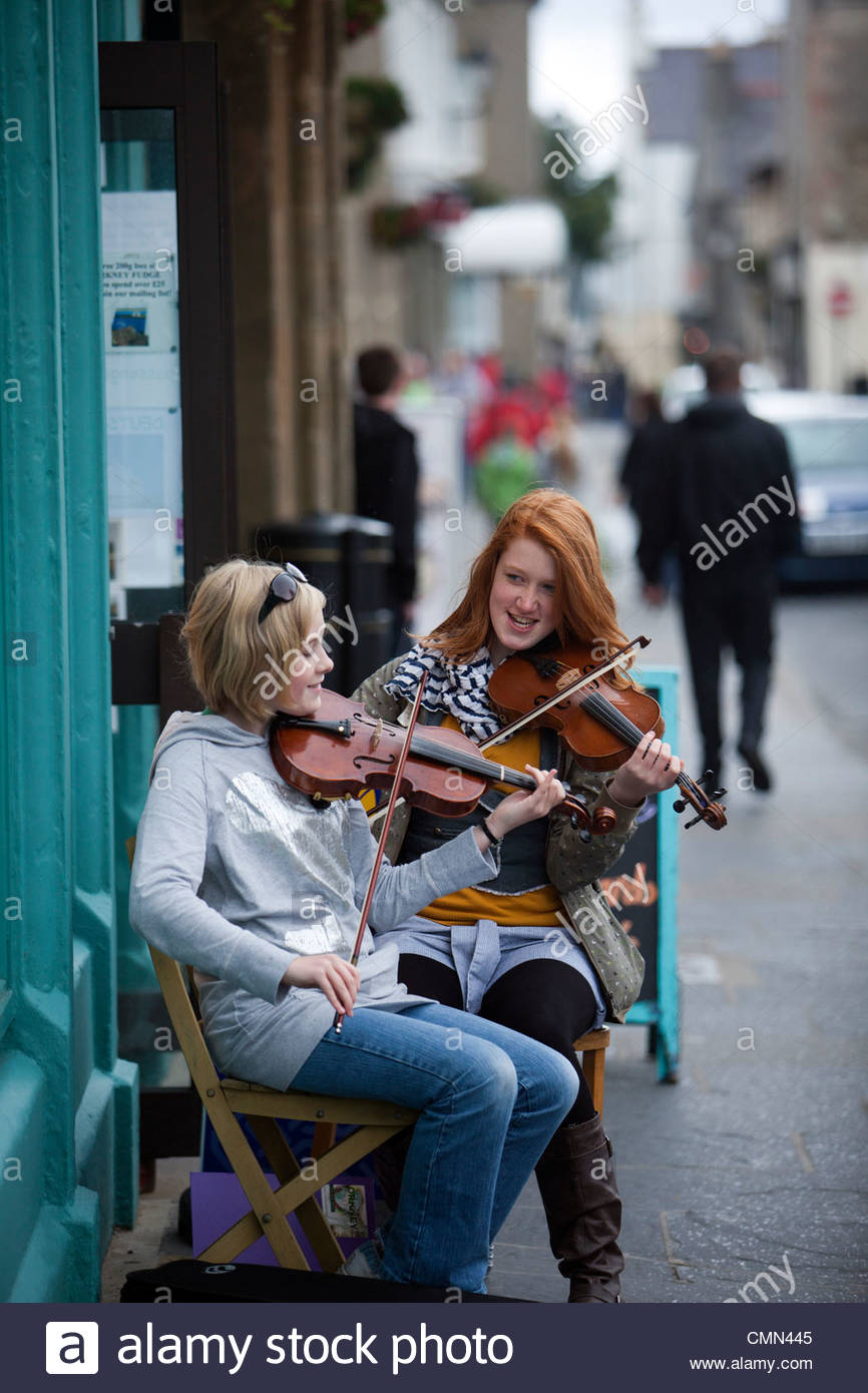 Young musicians busking in Kirkwall, Orkney, UK - Stock Image
