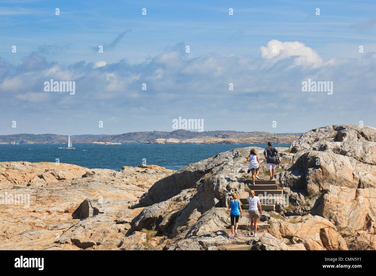 Females walking on a path at the sea - Stock Image