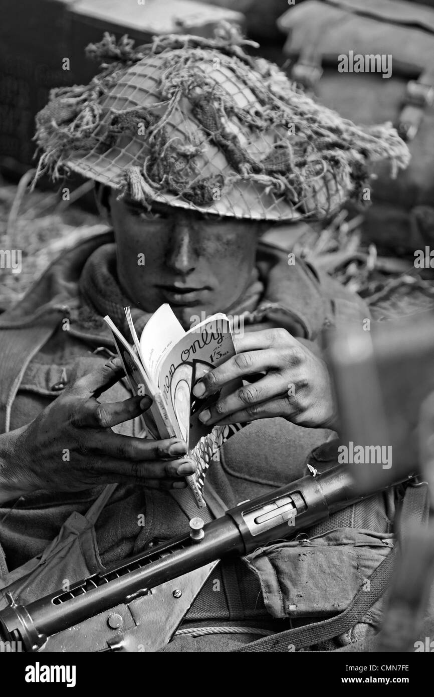 British Army Soldier (Looking to Camera) WW2 Reading Men Only July 1944 Monochrome - Stock Image