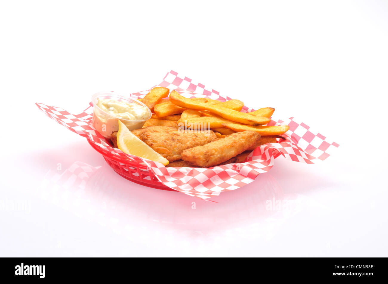 Basket of fish and chips with tartar sauce and lemon wedge - Stock Image