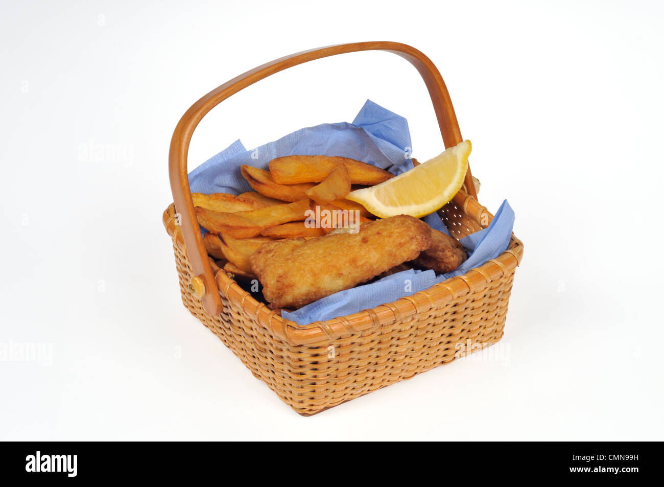 Basket of fried fish and chips with lemon wedge - Stock Image