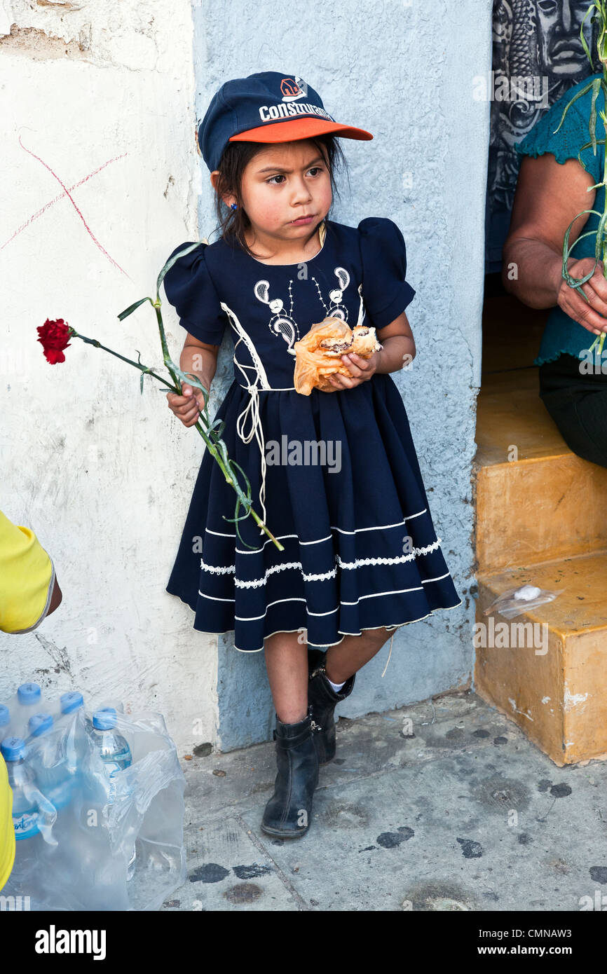 small Mexican girl holding red carnation eating lunch is skeptical about march down Alcala to celebrate microfinance - Stock Image