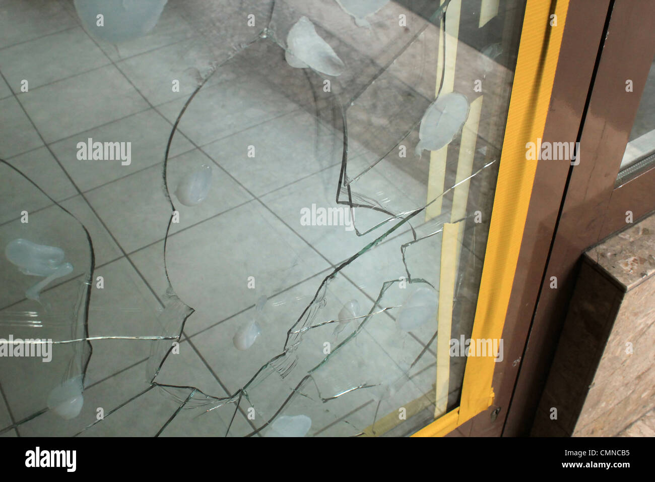 Broken glass of the entrance of a shop - Stock Image